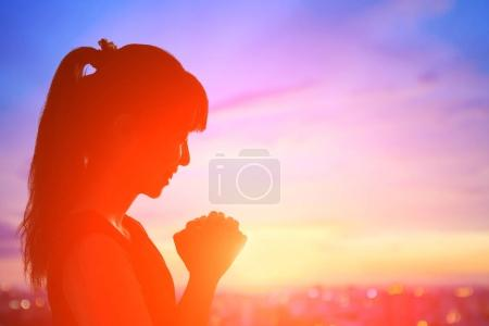 young woman praying  at  sunrise