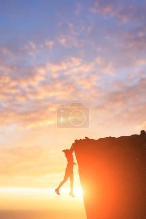 Businesswoman climbing on  cliff
