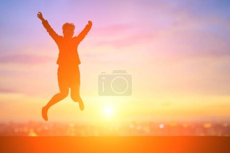 business woman jumping at  sunset