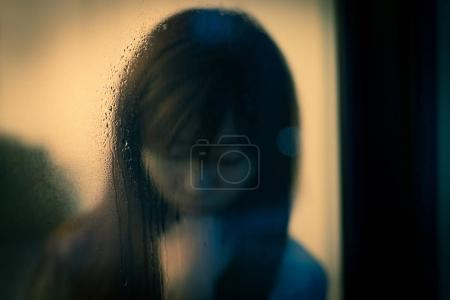 Photo for Woman feeling depression next to the window - Royalty Free Image