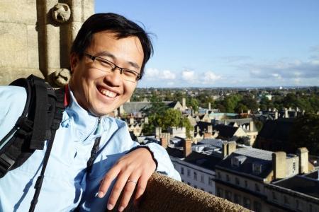 Photo pour Asiatique homme souriant joyeusement dans le bâtiment d'oxford - image libre de droit