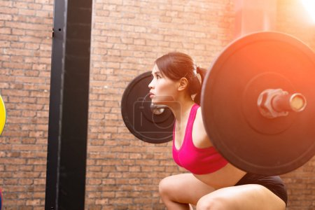 woman with barbell in the gym