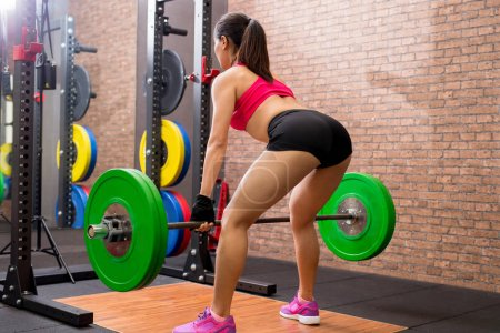 Photo for Woman training hard with deadlift in the gym - Royalty Free Image