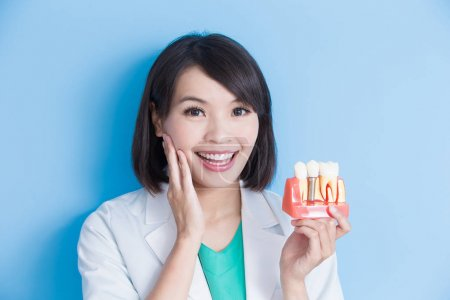 woman dentist with  implant tooth