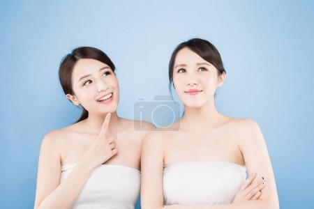 Photo for Two beauty women looking  somewhere  on the blue background - Royalty Free Image