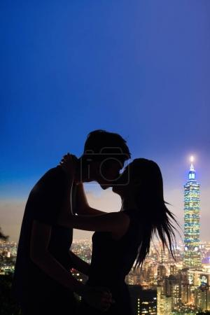 silhouette of couple kissing with night taipei city panorama in the taiwan