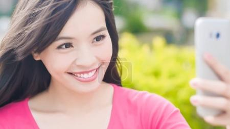 beauty woman taking selfie and smiling  happily in the park