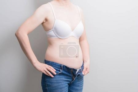 Fat overweight woman wearing  jeans on the gray background