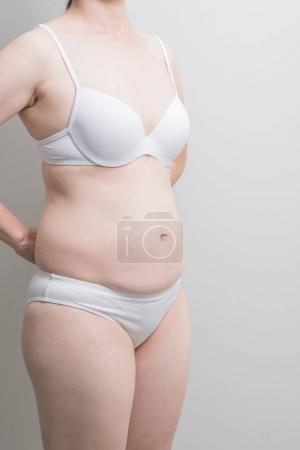 Fat overweight woman standing on grey  background, asian