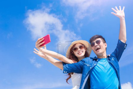 couple taking selfie happily with the blue sky on background