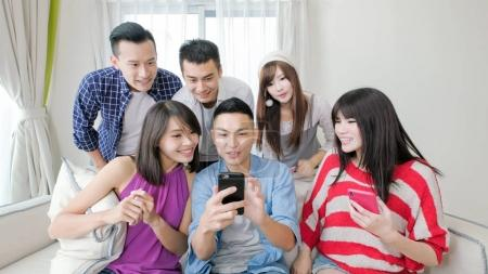 young people using  phones and smiling  happily