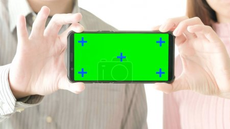 people holding  cell phone with green screen at home