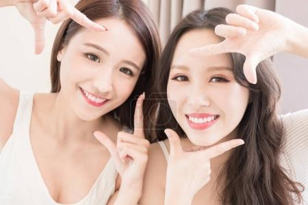 two beauty women making frame gesture at  home