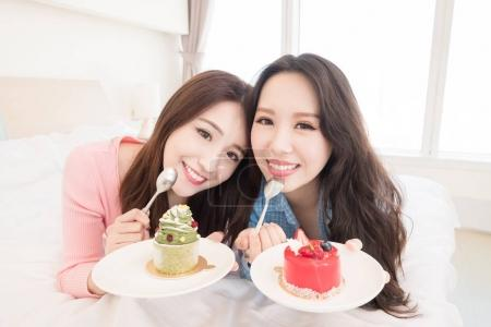 two beauty women eating  cakes on the bed