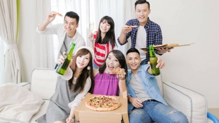 young people eating  pizza and drinking  beer on  party