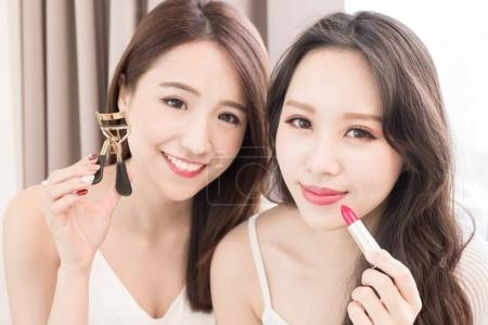 two beauty women with  mascara and clip eyelashes