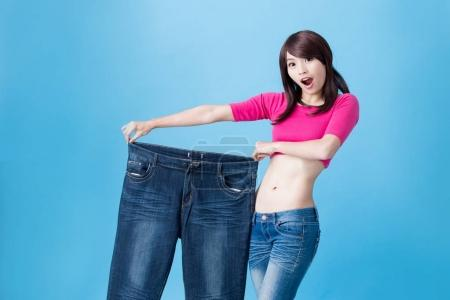 woman showing  weight loss on the blue background