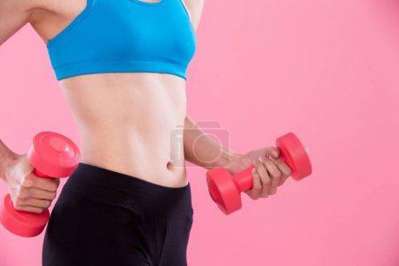 beauty sport woman with  dumbbell on the pink background