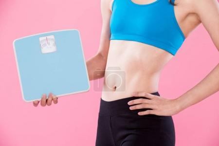 sport woman with  weight scales on the pink background