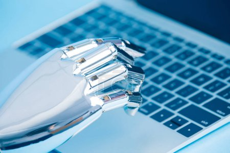 robot hand using  notebook on the blue background