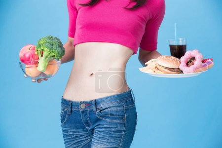 woman with fruits and vegetable and  junk food on the blue background