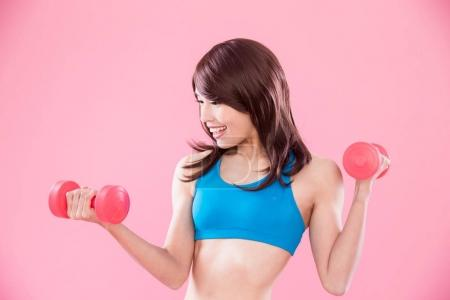 beauty sport woman with dumbbells  on the pink background