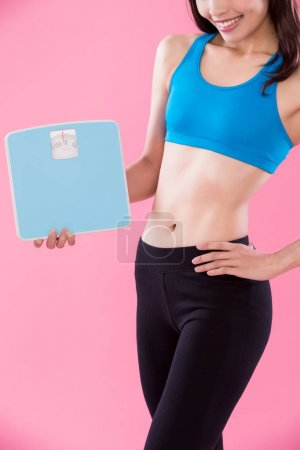 sport woman holding  weight scales  on the pink background