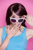 surprised woman wearing  sunglasses  on the pink background