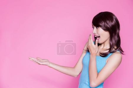 surprised  woman  showing  something to you on the pink background