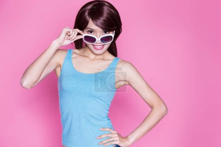 woman wearing  sunglasses and smiling  happily on the pink background