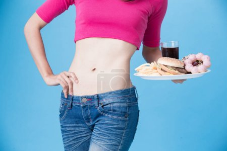 woman with  unhealthy food  on the blue background