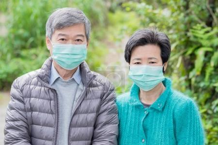 old couple wearing masks on  the mountain