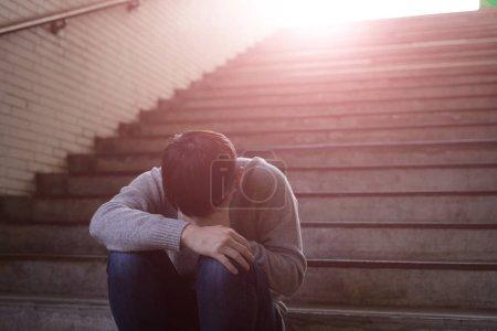 depressed man feeling  upset and sitting  in underground
