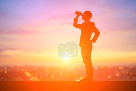 Photo pour Silhouette d'homme d'affaires avec des jumelles au coucher du soleil - image libre de droit