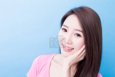 woman wearing  braces  smiling  happily on the blue background