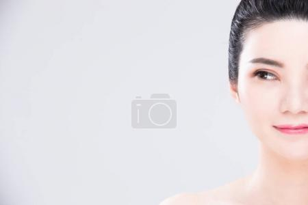 woman looking  somewhere. beauty skin care concept on the gray background