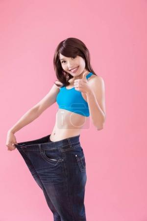 woman wearing oversized  jeans on the pink  background. woman showing thumb up