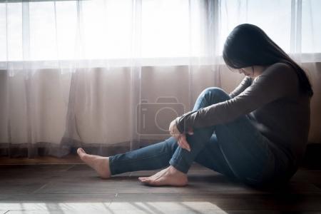 depressed woman sitting  on floor  in the room