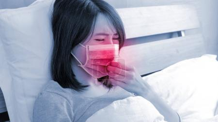 woman with fever lying on the bed