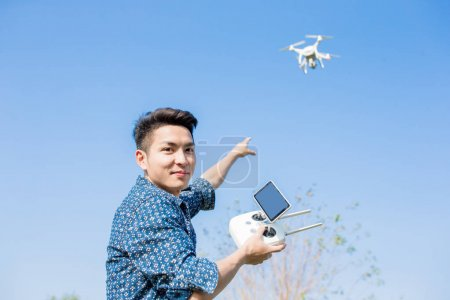 man playing with  drone and pointing