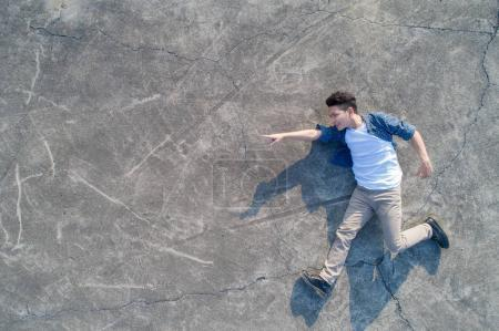 top view  of man feel  lying on the floor pointing