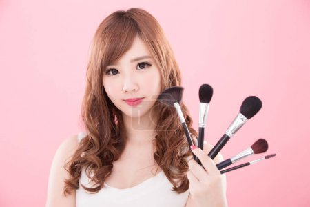 beautiful  woman with makeup brushes  on the pink background