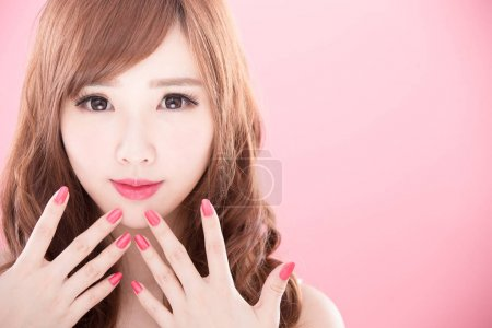 Beauty woman showing  her nails on the pink backgr...