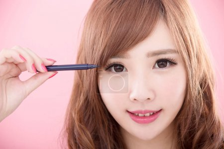 beauty woman with  eyeliner on the pink background