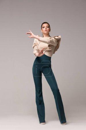 Photo pour Modèle de femme dans des vêtements élégants à la mode posant en croissance dans le studio. Chemisier beige à manches longues luxuriantes, pantalon long évasé vert à taille haute. Les mains en face de vous . - image libre de droit