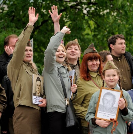 Orel, Russia - May 9, 2017: Victory Day selebration. Smiling people in Soviet war uniform waving hands in Immortal Regiment