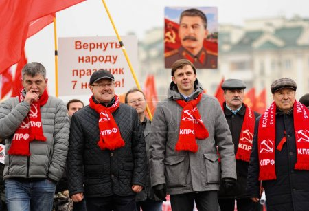 Orel, Russia, November 7, 2017: October Revolution anniversary meeting. Orel Governor Andrey Klychkov and Government members in red Communist scarves with Stalin portrait