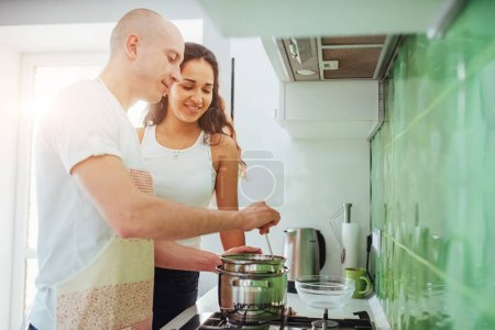 Happy young couple preparing on the stove.