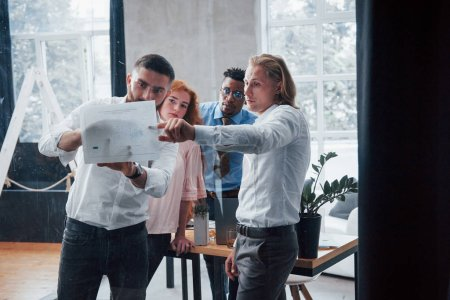 Photo for Man with blonde hair explain certain things. Young multiracial team in official wear at office looking at price list. - Royalty Free Image