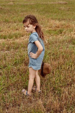 Little girl standing in the field with a hat in her hand.
